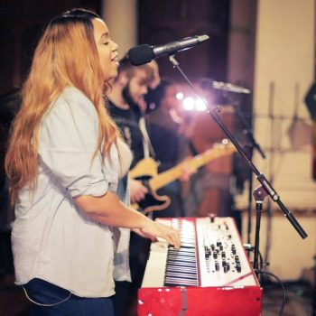 A woman playing the keyboards and singing into a microphone.