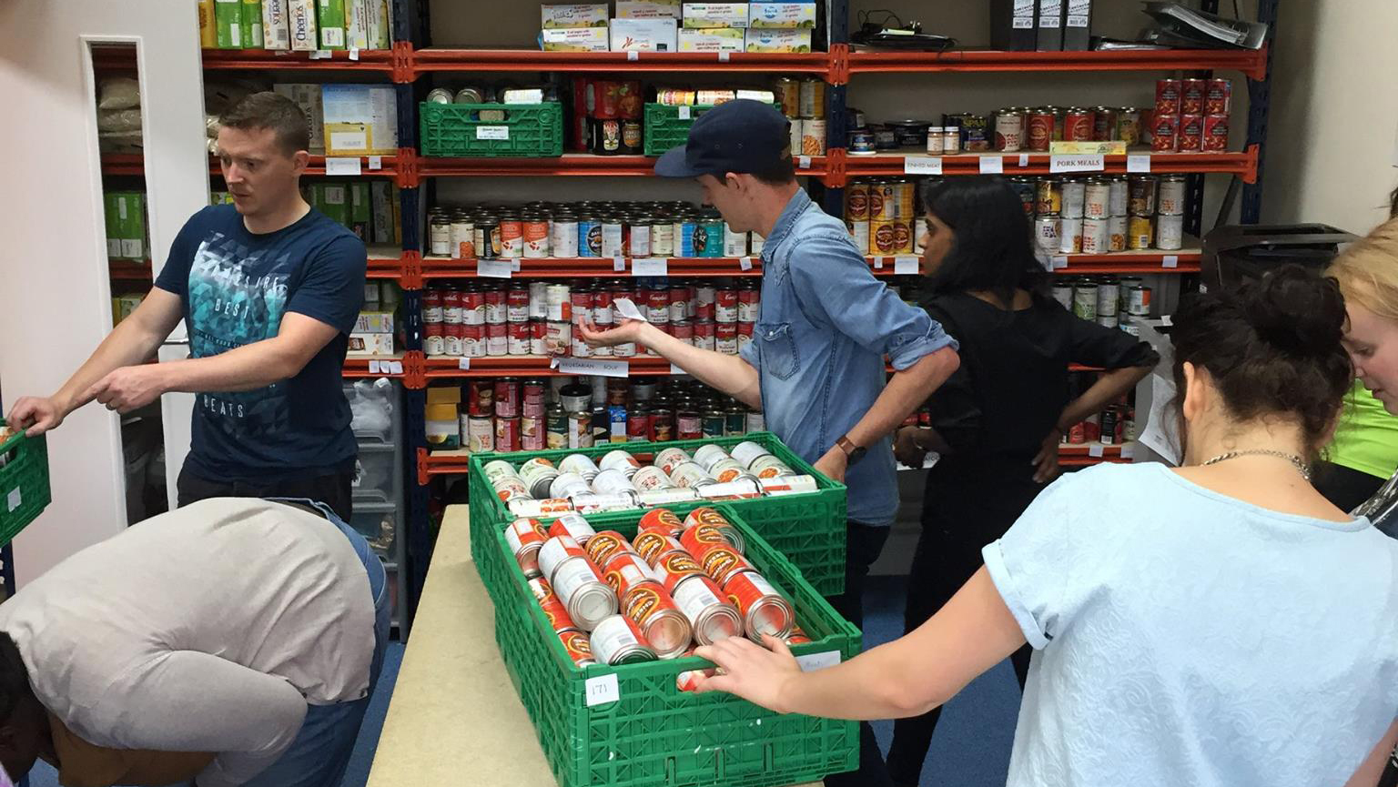 People distributing cans of food stacked on shelves in a storeroom.