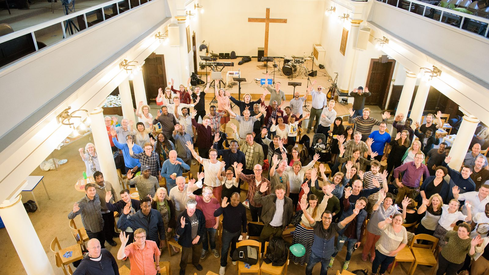 Lots of people in a church, waving and smiling.