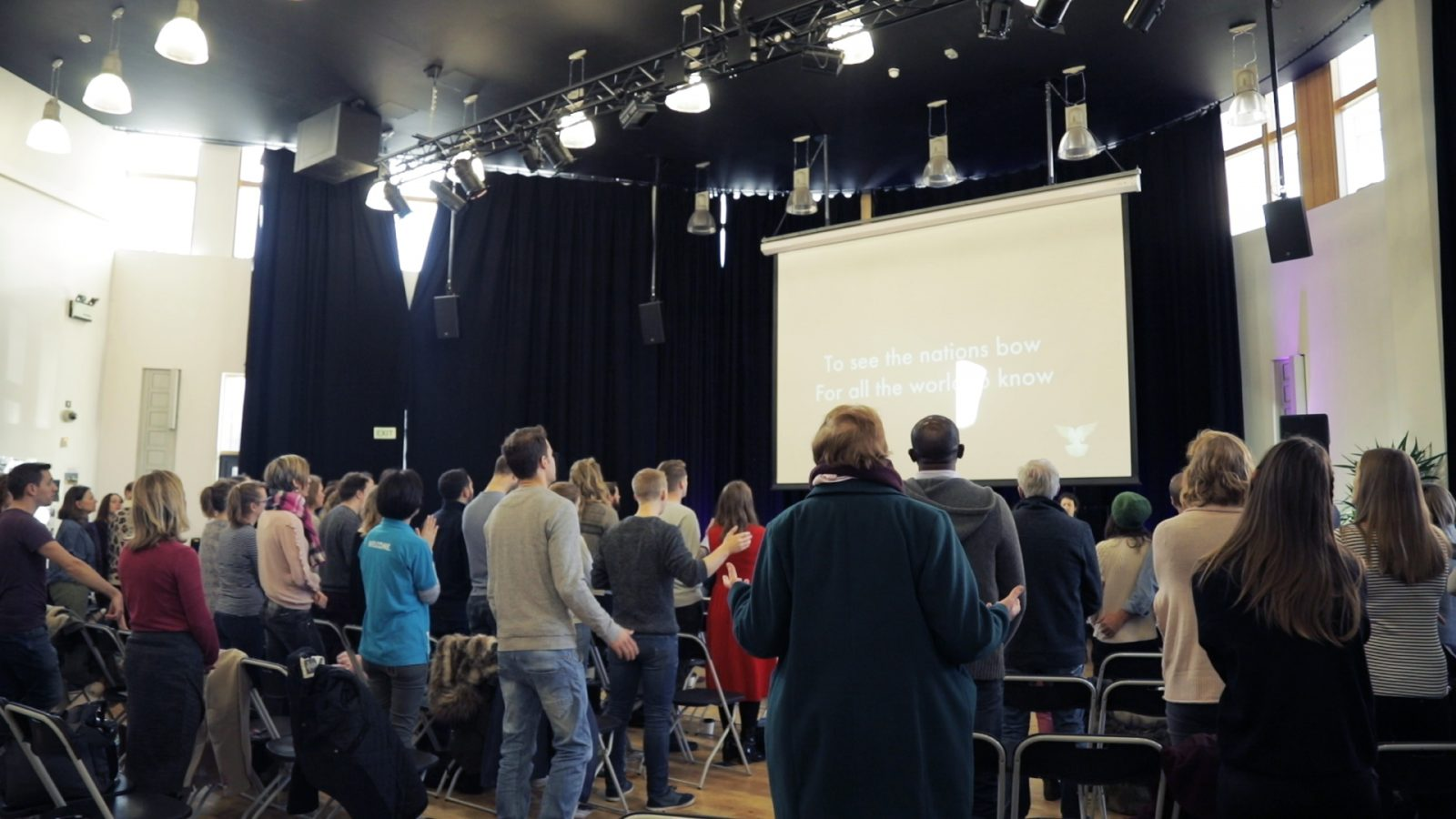 People worshipping in a school hall in Stockwell.